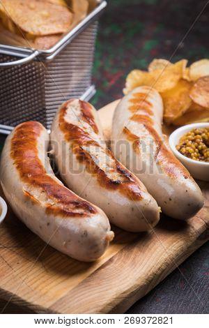Grilled german sausages with mustard and fried potato chips stock photo