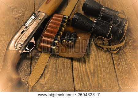 Hunting rifle and ammunition lie on wooden background. stock photo