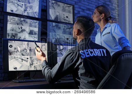 Security guards monitoring modern CCTV cameras indoors stock photo