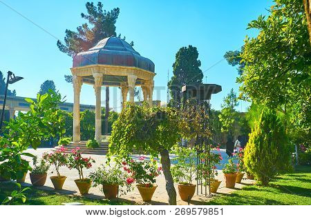 The site of Hafez Tomb is located in beautiful Mussala Gardens with lush trees, trimmed bushes and flowers in pots, Shiraz, Iran. stock photo