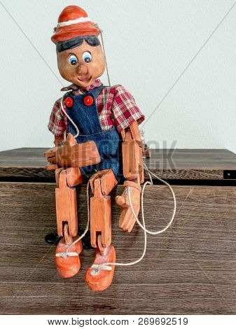 Traditional puppets made of wood.Sit on a pine wood cabinet. stock photo