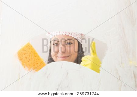 Woman wearing yellow gloves and bandana holding orange sponge in one hand with thumb up smiling from behind shower glass stock photo