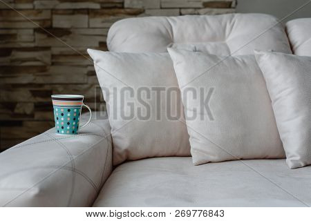 A cup of coffee or tea on a white sofa with sofa cushions, a sofa in the living room at home. comfortable hotel room. Stress relief in a cozy atmosphere. stock photo