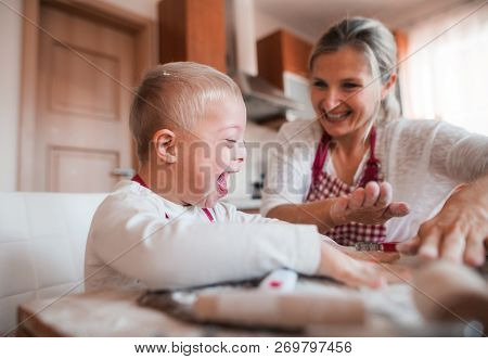 A laughing handicapped down syndrome child with his mother indoors baking. stock photo