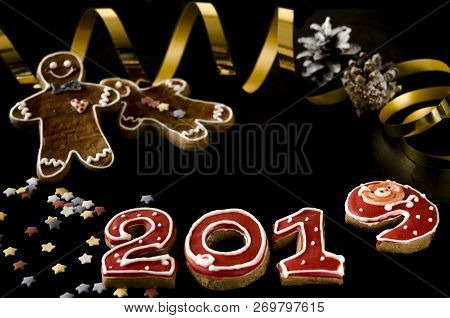 New Year card on black background gingerbread red numbers 2019 with multi-colored stars, gingerbread Mans stock photo