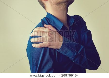 Closeup of young man with shoulder pain, Upper arm pain, People with body-muscles problem, Healthcare And Medicine concept. Businessman is holding a patients hand. stock photo