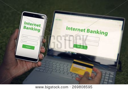 Man browsed homepage of internet banking service on his smartphone and laptop holding credit card. Online payment mobile banking concept. Written words Internet banking on phone and notebook screens stock photo
