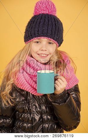 Girl In Hat, Pink Scarf, Black Jacket With Mug. Child With Blue Cup Smile On Orange Background. Hot
