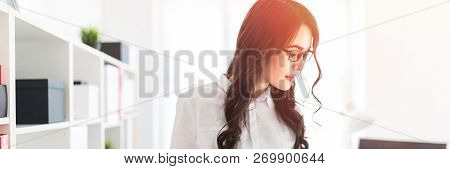 Beautiful young girl stands in the office thumbs a folder with documents. stock photo