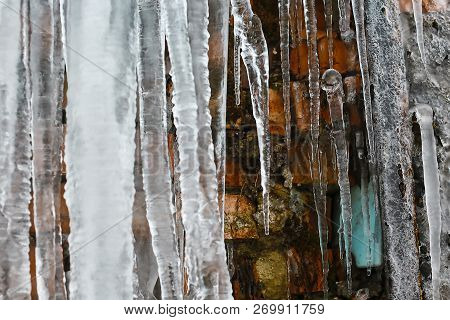 closeup icicles, abstract old brick wall background with crack ice, moss, and branches of bushes, icicles, ice build-up on brick wall. stock photo