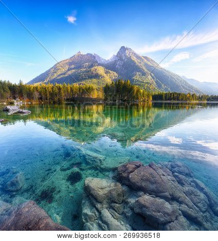 Fantastic autumn sunset of Hintersee lake. Beautiful scene of trees near turquoise water of Hintersee lake. Location: resort Ramsau, National park Berchtesgadener Land, Upper Bavaria, Germany Alps, Europe stock photo