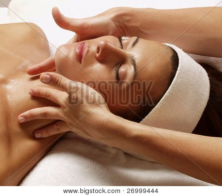 Beautiful young woman getting a face treatment at beauty salon. stock photo