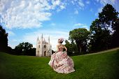 A lady like a princess in a vintage dress before the enchantment mansion