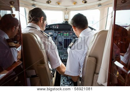 Rear view of pilot and copilot in cockpit of corporate jet stock photo