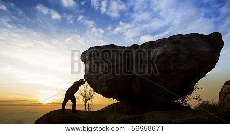 Man pushing a boulder on a mountain stock photo