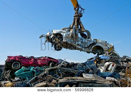 Crane picking up a car in a junkyard stock photo