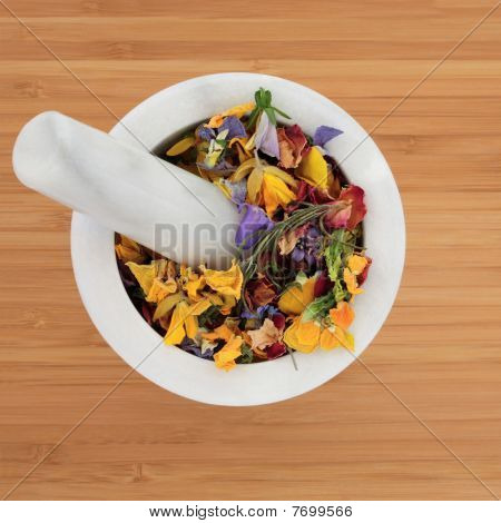 Pot Pouri dried herb and flower mixture in a marble mortar with pestle over bamboo mat background. stock photo