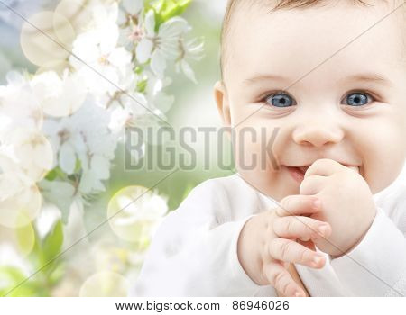 childhood, babyhood, summer, spring and health concept - closeup of happy baby boy or girl over gree