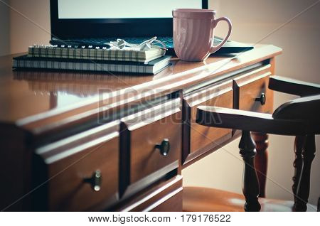 Writing desk with laptop stationery items cell phone and mug of coffee. Antique vintage furniture style. Business office or home workspace concept. Toned image selective focus