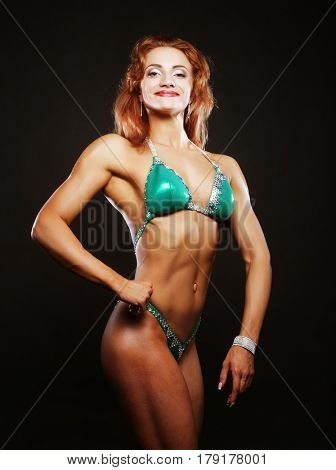 blond bodybuilder woman in bikin on black background stock photo