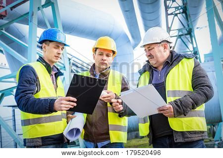 Engineers discussing maintenance of a petrochemical plant. Technical inspection. Oil and gas industr