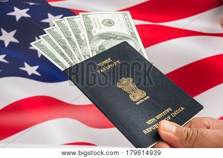 concept showing Indian passport with US currency notes or Dollars with american flag in the background, applying for US / american tourist or H-1B visa stock photo