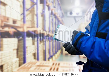 Closeup shooting hand of QC. worker checking goods on delivery in the cold room warehouse. Logistics food and beverage in cold storage concept