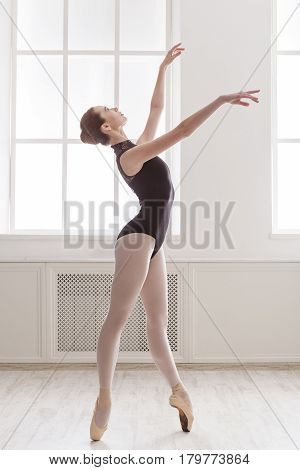 Classical Ballet dancer training. Beautiful graceful ballerina in black on pointe near large window in light hall. Vertical image