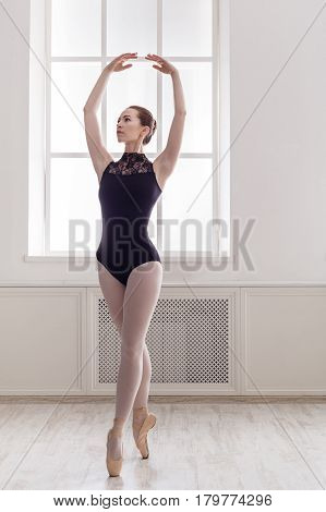 Classical Ballet dancer portrait. Beautiful graceful ballerina in black on pointe near large window in light hall. Ballet class training, high-key soft toning. Vertical image