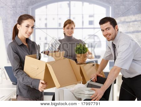 Young office workers moving office, unpacking boxes, smiling.? stock photo