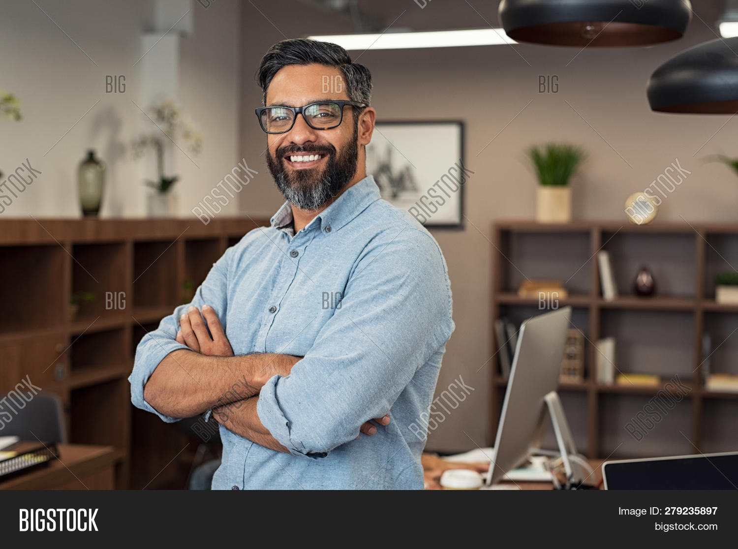 Portrait of happy mature businessman wearing spectacles and looking at camera. Multiethnic satisfied