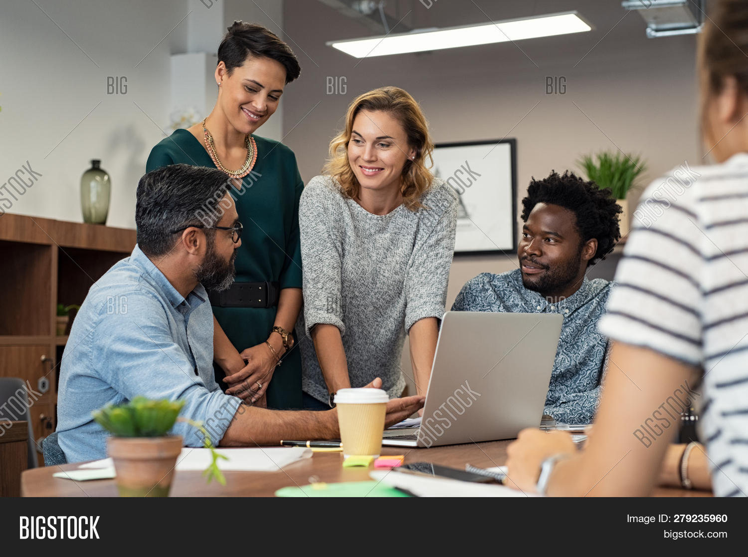 Multiethnic business people talking and smiling during meeting in office. Mature middle eastern man