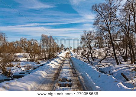 Country road in early spring. On the edges of the road snow drifts stock photo