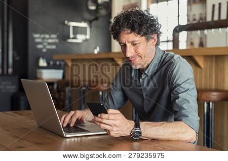 Happy mature business man sitting at cafeteria with laptop and smartphone. Businessman texting on sm