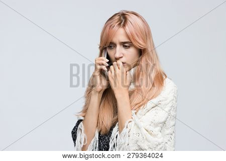 Studio portrait of blonde girl in white sweater talking on the phone, nervous conversation, sad look/ found out what happened, bad news, nervous feeling, experiences of fear/ people concept. stock photo