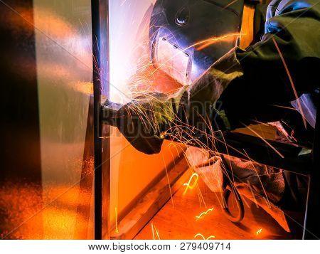 Welder Worker Performs Jump Welding. Worker Welder Performs Arc-Welding Process of Metal Structures. Flying Sparks From the Welding Machine. Welder Welds Metal Profiles for Second Floor Indoors stock photo