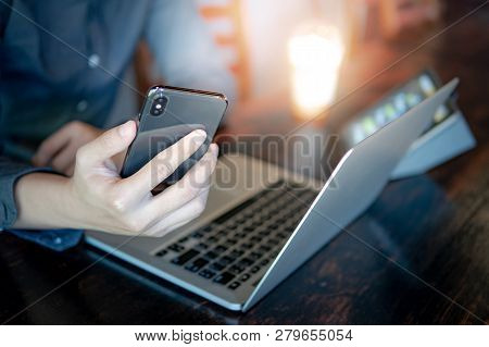 Male Hand Holding Smartphone. Businessman Using Laptop Computer And Digital Tablet While Working In