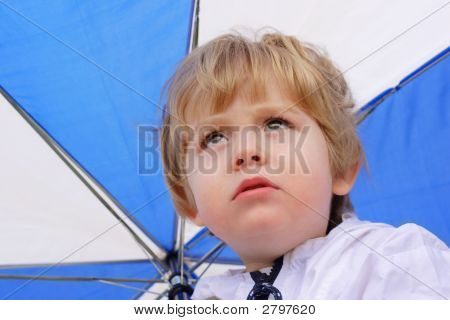 A young boy holding an umbrella looks up to the sky with a forelorned look stock photo
