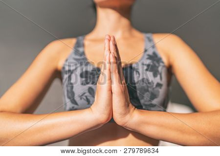 Yoga namaste woman meditating yoga mudra with closed hands together in prayer pose praying for gratitude. Zen meditation wellness in morning sun. stock photo