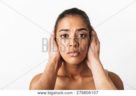 Scared young african woman sitting while man's hands covering her ears isolated over white background stock photo