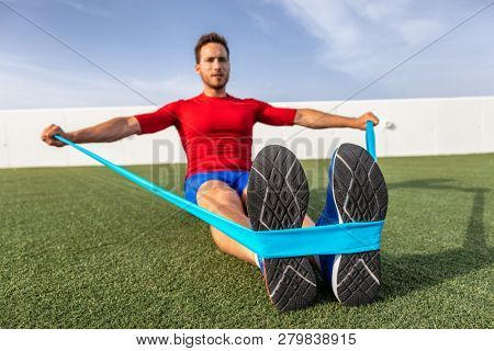 Fitness man training arms with resistance bands at outdoor gym or home garden. Body workout with equ