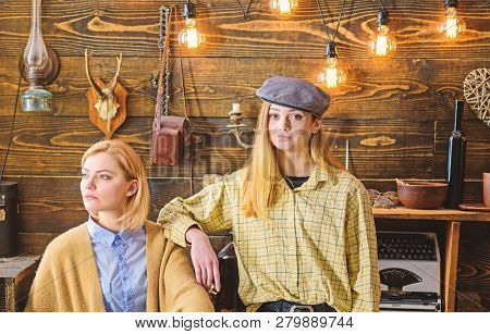 Friends or sisters spend pleasant evening in gamekeepers house, interior background. Girls enjoy vacation. Girls on calm faces enjoy warm atmosphere while having rest. Vacation in woods concept stock photo