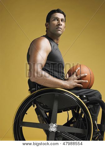 Side view of a confident paraplegic athlete in wheelchair holding basketball against yellow background stock photo