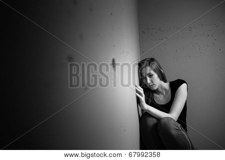 Young woman suffering from a severe depression (very harsh lighting is used on this shot to underline/convey the gloomy mood of the scene) stock photo