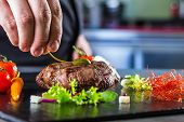 Chef in inn or eatery kitchen cooking, just hands. Arranged meat steak with vegetable decorati