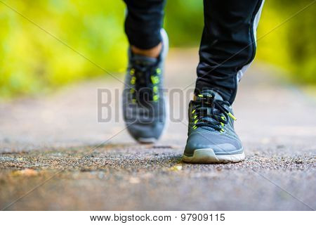 Close-up on shoe of athlete runner man feet running on road