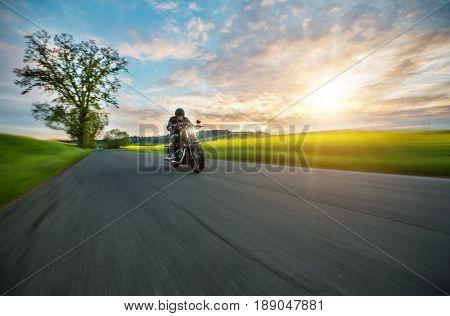 Dark motor-biker riding high power motorbike in nature with beautiful sunset light. Travel and transportation. Freedom of motorbike riding stock photo