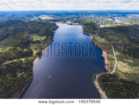 Beautiful view from a road going through the beautiful lake and forest surrounded with water on both sides shot above from drone aerial vibrant picture stock photo