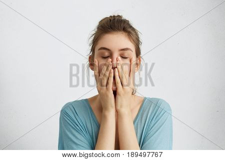 Headshot of young beautiful student female closing her eyes holding hands on chin being tired after hard work trying to relax for a minute and to gather her thoughts. Tiredness feelings concept stock photo