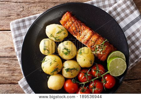 grilled salmon and boiled new potatoes with butter and herbs closeup on a plate. horizontal view from above stock photo